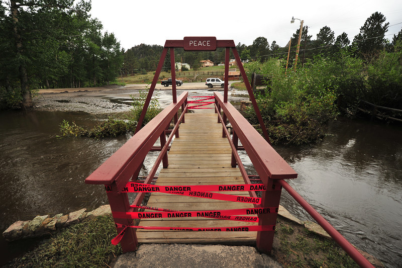 A bridge is blocked by tape at St. Bart's along MacGregor Avenue on Wednesday. Bridges of all sizes were damaged by the flood.
