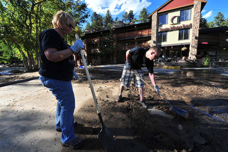 Nancy and Tylor Waller work to level the mud-covered parking lot at Silver Moon on the west end of Elkhorn Avenue on Saturday. The lot was just a part of the river a week ago.