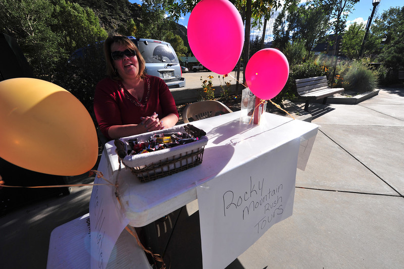Lori Hewitt of Rocky Mountain Rush Tours sets up shop on the sidewalk along Elkhorn Drive on Saturday. The business' office was flooded, so they moved outdoors to stay in business during clean up.
