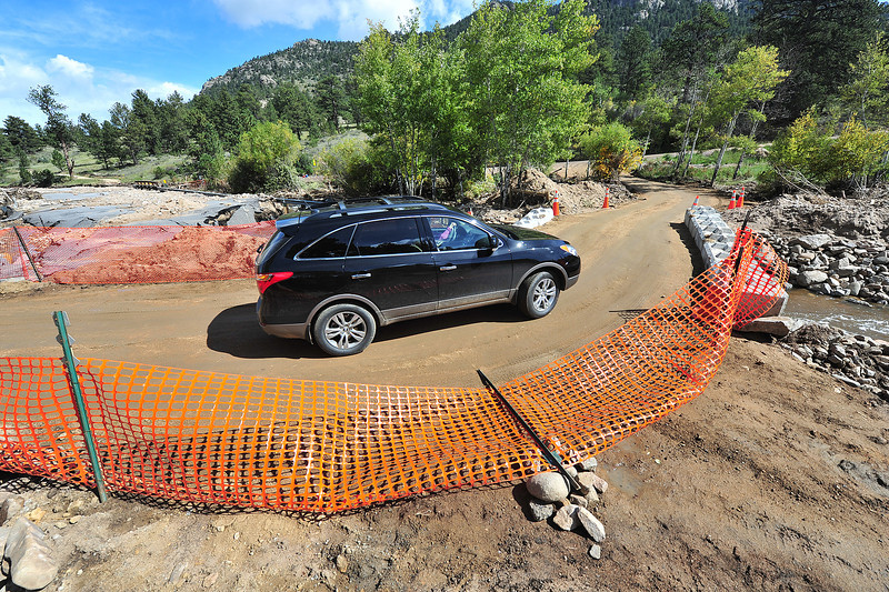 A SUV crosses the temporary bridge into Little Valley on Monday. The bridge across Fish Creek is a sign of progress and the slow, eventual return to normalcy.