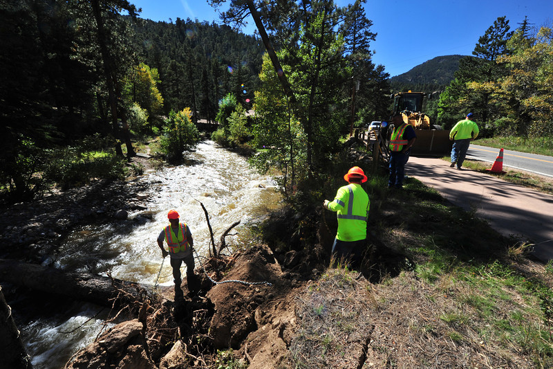 Lafayette Public Works employees attempt to haul a downed tree out of the Fall River on Tuesday. Many communities are helping the afflicted towns in Colorado.