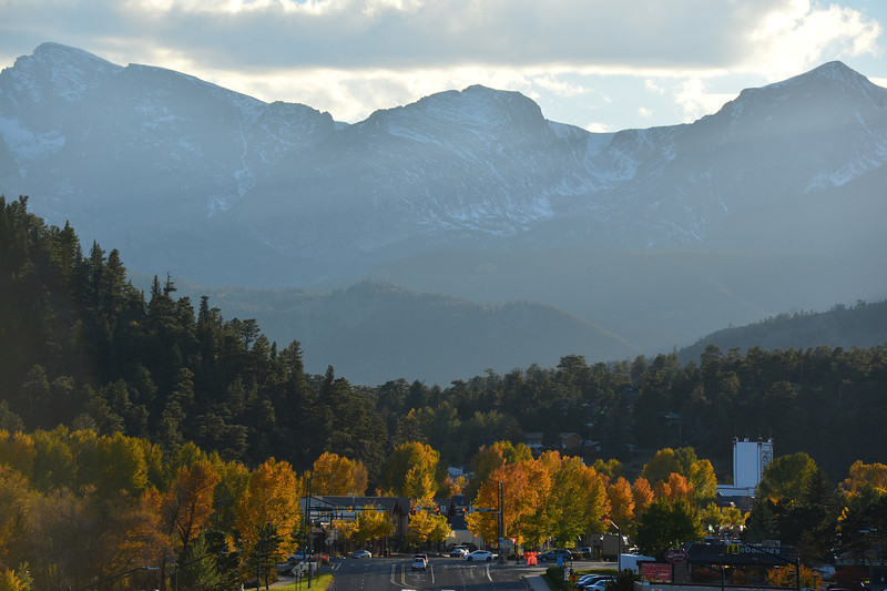 The divide peaks tower over Estes Park as evening sun lights the fall foliage in downtown. Estes Park is the northern end of the Peak to Peak Scenic Byway, and a natural destination for fall sightseers.