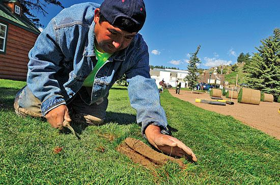 Vicente Hernandez matches up seams of sod in Bond Park on Saturday.