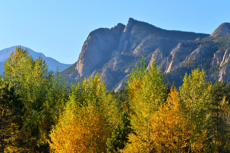 Lumpy Ridge towers over fall-colored trees on Big Thompson Avenue. The ridge is named for its craggy cliffs and top.