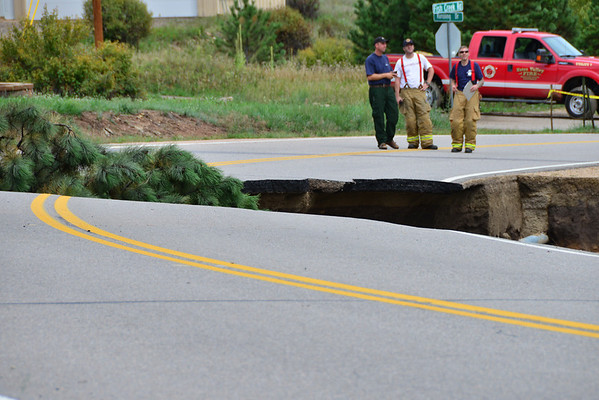 Fire department officials inspect the damage to Fish Creek Road near the intersection of Sandborn and Fish Creek. Floodwaters have washed out the road.