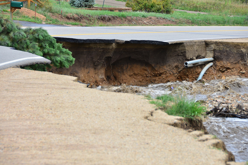 Broken pipes are exposed where Fish Creek has washed out the Fish Creek Road near the road's intersection with Sandborn in Carriage Hills.