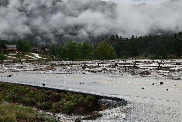 Low hanging clouds create a surreal scene Friday morning, Sept. 13 as floodwater from Fish Creek carry debris.