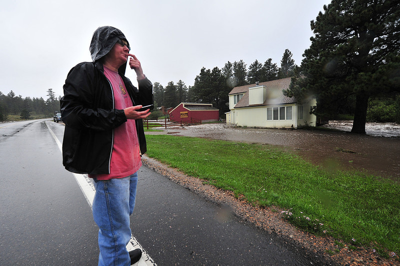 Cindy Knight can only watch as the Fish Creek rises around her house on Thursday. While the flood waters were taking her back deck off, her concern was for her cat trapped inside.