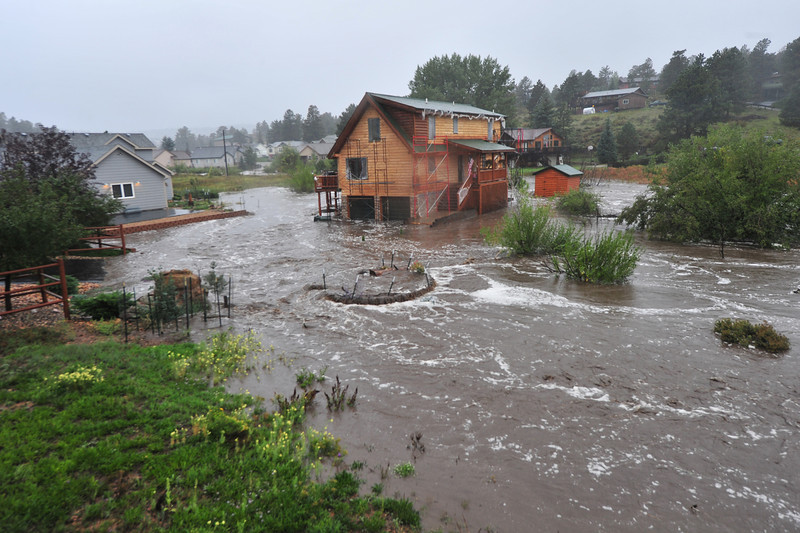 A house with people still inside is completely surrounded by the Fish Creek on Thursday. Flooding closed roads and neighborhoods around Estes Park as heavy rain soaked the entire Front Range.