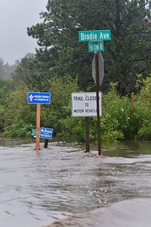 Signs stick out of the flood waters of Fish Creek Road on Thursday. The intersection was closed and eventually collapsed in the flood waters.
