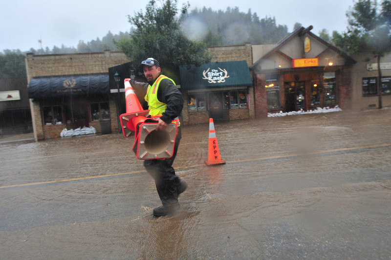 Town employees place cones to narrow Elkhorn Avenue as water from the Big Thompson River overriun its banks. Officials are comparing the flood crest to that of the Big Thompson Canyon Flood of 1977.