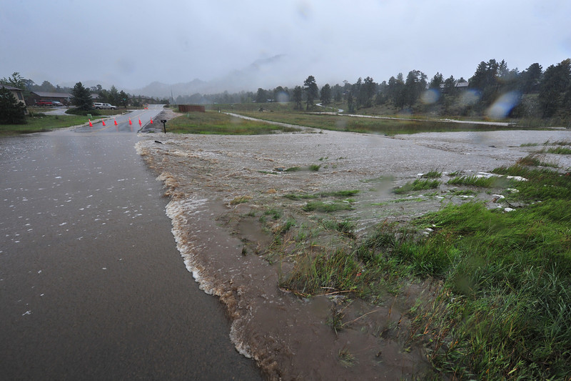 A usually small creek overruns its banks and closes Carriage Drive on Thursday. The floodwaters made travel in Estes Park difficult, at best, and often dangerous.