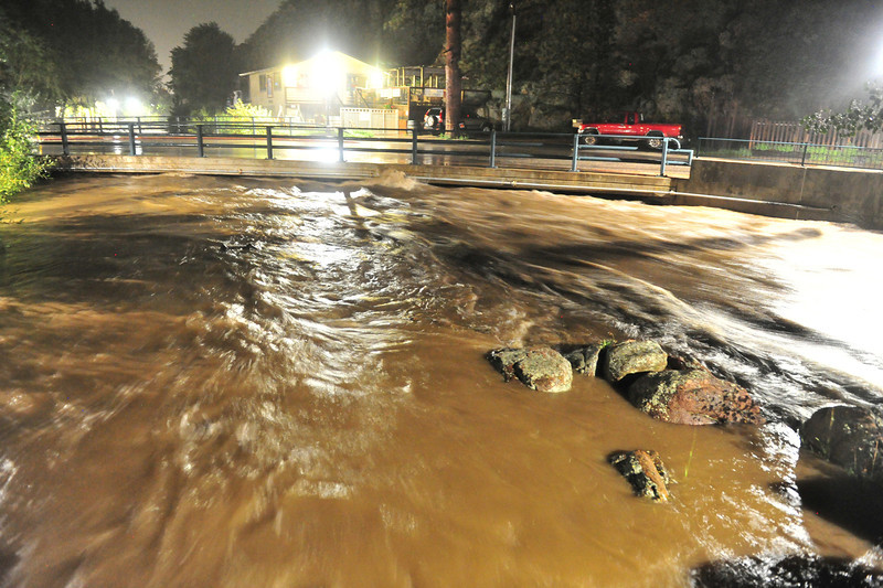 Mocha-colored water from the Big Thompson and Fall rivers splash over the bridge on East Riverside Drive on Thursday morning. Heavy rain has led to closures of Hwys US 34, US 36, and SH 7, as well as a dam breach leading to flooding from Big Elk Meadow down to Lyons.