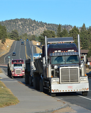 Trucks being used to haul in repair materials for Hwy/ 34 are parked along Big Thompson Avenue as their drivers stop for a refreshment break Wednesday afternoon.