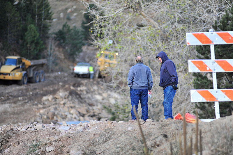 Friends watch and talk as crews continue reconstruction efforts at the entrence to Big Elk Meadows on Wedneday. With US 36 now open, people can see a bit more of the impact of the September flood.