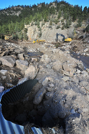 Crews work on the road into Big Elk Meadows, above a clogged culvert, the culprit in much of the destruction in the area. A temperary road into Big Elk Meadows is complete, but a more perminent road is underconstruction.