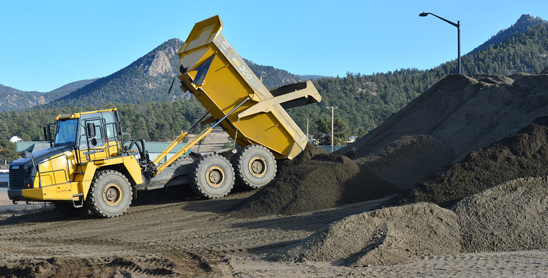 A earth hauler dumps a load of sand at the Fairgrounds at Stanley Park. The material, much of which was washed into Lake Estes during the September flooding,  was recently removed from the lake and will be used to rebuild roads damaged by the flood.