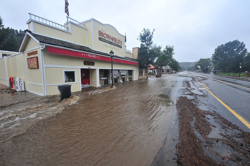 Water rushes past Brownfields on Elkhorn Avenue on Thursday. Much of the tourist economy of Elkhorn and Estes Park will be disrupted by the historic flood.