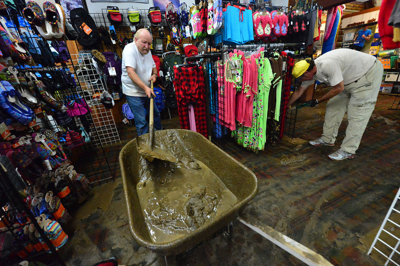 Friends and volunteers help clear mud from Outdoor World on Saturday. Many businesses along Elkhorn Avenue found mud covering their floors when they got to the stores.