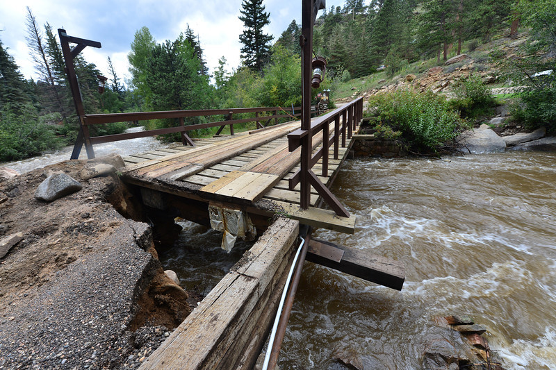 A bridge over the Big Thopson River sits damaged and unusable on Saturday, isolating the Glacier Lodge. The bridge withstood years of spring runoff only to be nearly swept away by flood waters this week.