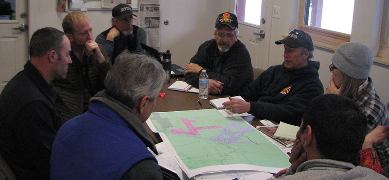 Steve Childs, at the head of the table, attends a meeting with the Larimer County Conservation Corps and Larimer County Workforce in discussions about flood plain determinations and the upcoming spring runoff.
