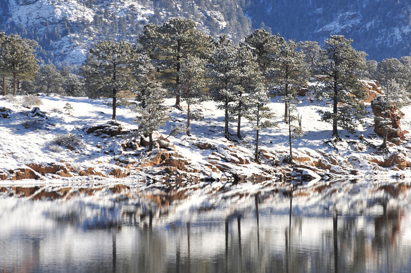 Trees, rocks and snow reflect on Mary's Lake on Sunday. Due to the constant change in the water level, the lake rarely freezes over.