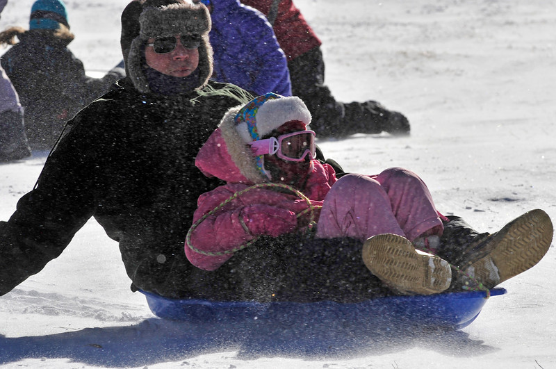 Eveyn Mason, 9, and Tim Mason, of Longmont slide down the slope of the Hidden Valley Snowplay Area on Sunday. While temperatures dipped and the wind howled, spirits were high as visitors flocked the the slope in the national park.