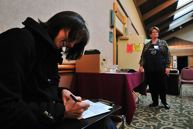 Elizabeth Gosnell fills out the back of her ballot envelope while election judge Dottie Allen at the Rockie Mountain Park Inn polling place on Tuesday. While many Estes Park voters took advantage of early voting, many waited until Election Day to cast a vote.