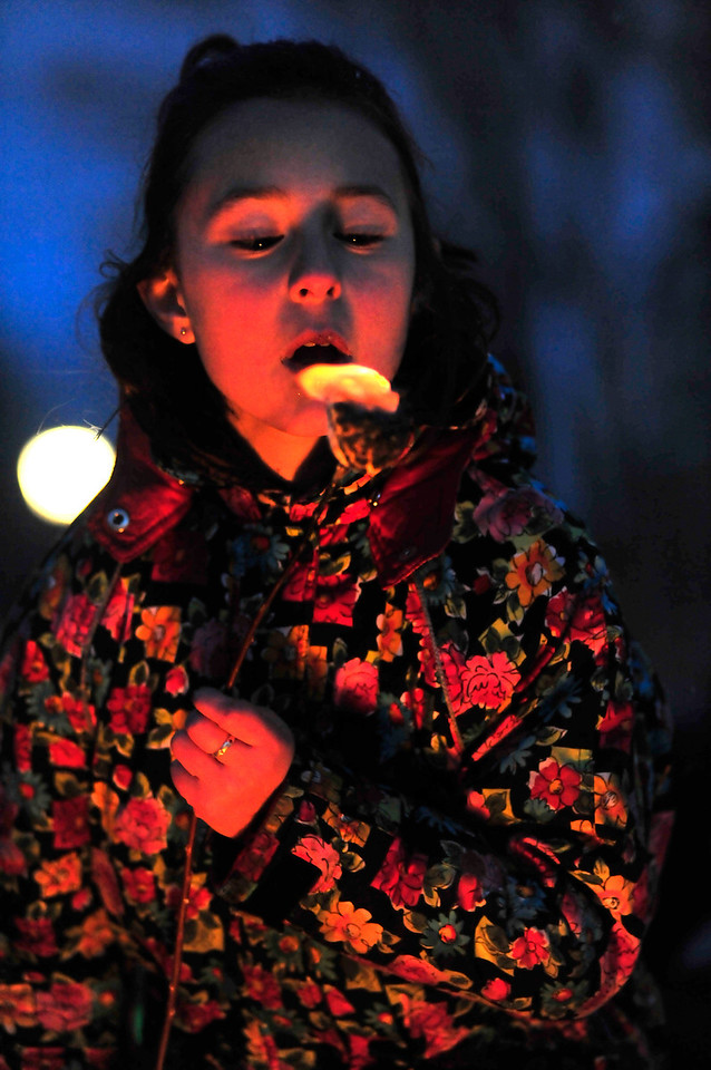 A child enjoys a flaming marshmallow at the tree lighting. Arrive early for best chance of marshmallow roasting.