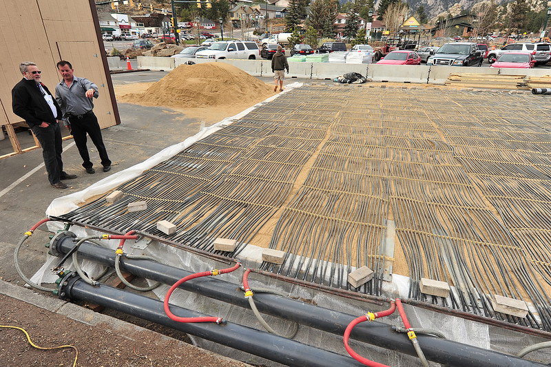 Town officials inspect the cooling tubes at the temperary ice rink taking shape along East Riverside and Elkhorn avenues on Monday. While only temperary, the project seems elaborate.