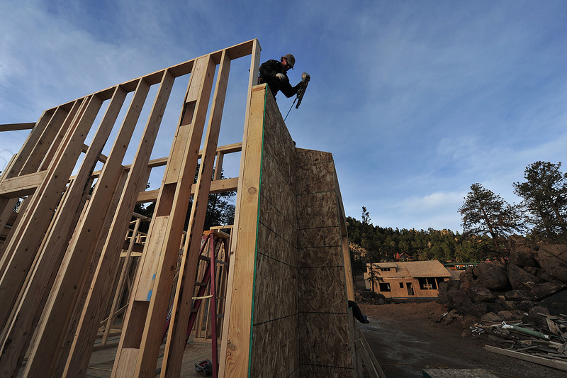 Kevin Cooper frames a house in Woodland Heights on Monday. Many new houses are rise, some literally, out of the ashes of the June fire in the neighborhood on the west edge of town.