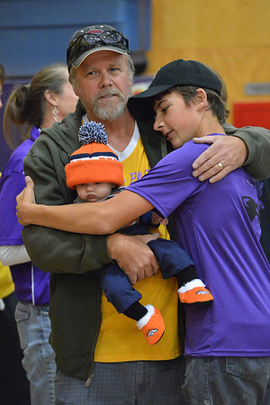 Alex Franklin, right hugs his father and his nephew after receiving a replacement letter jacket and yearbook from the high school student council at the pep ralley on Friday. Franklin, his two siblings and junior Becky Reilly all lost the jackets, yearbooks and homes in the June Woodland Heights fire.