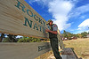 The national park's Tony Aiuppa repaints the entrance sign at park headquarters on Wednesday. While fire crews battle the Fern Lake Fire, the rest of the park and its crews must carry on.