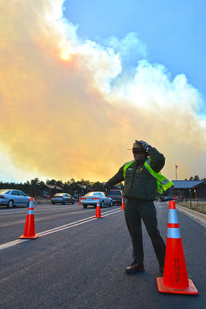 Ranger Kelly Azatt keeps a lane open for emergency vehicles at the Beaver Meadows entrance station on Tuesday. The fire above Fern Lake grew to over 300 acres over the afternoon and and evening.