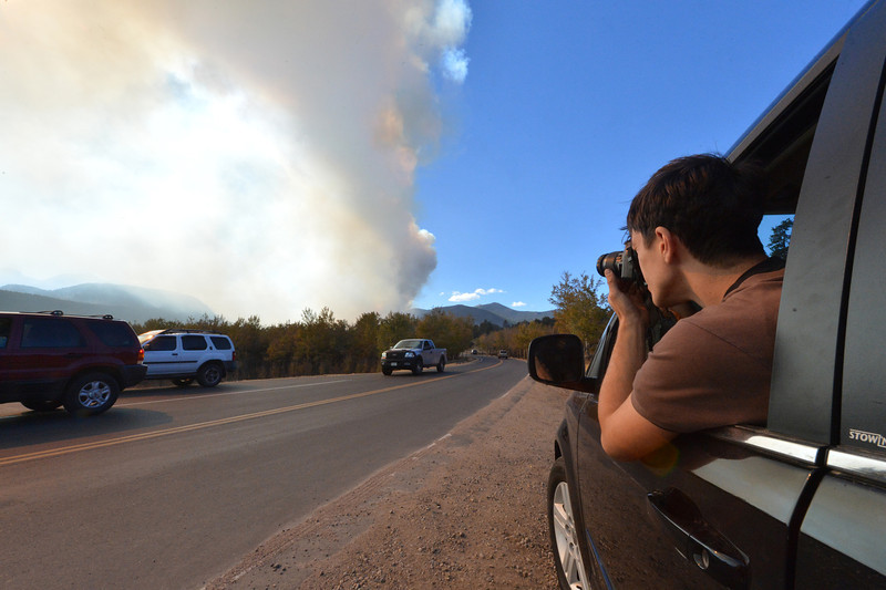 Josh Bradley, London, England, stops to photograph the smoke plume on his way out. Bradley and his wife had stayed in the Moraine Park Campground on Monday night and were already planning to leave when the campground was evacuated.
