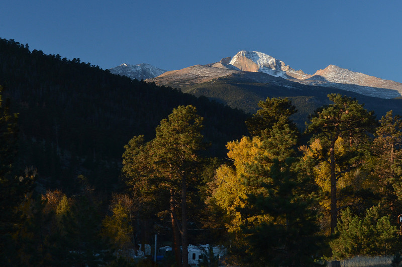Snow-dusted Longs Peak towers above Estes Park on Sunday morning. The cool morning gave way to a clear and slightly warmer fall day.