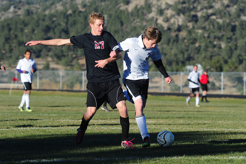 Zach Pierce gets hooked by Community Christian's Charles Wittman on Wednesday. Pierce scored the fourth of the Bobcats' goals in their 4-1 win.