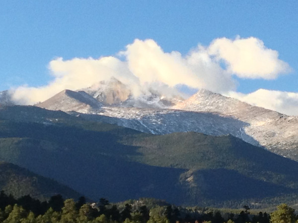 Clouds roll over Longs Peak on Tuesday, hinting at the change to come. We should be warm, though windy today with a high one the mid to upper 60s. Clouds and rain are expected to roll in this afternoon.