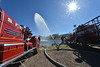 Several vintage fire trucks sit at Lake Estes, while one pumps a high arching stream of water into the lake. The pumper truck was featured in a documentary as Doug Klink restored it to working condition.