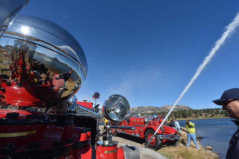 Firetruck fans, friends, a water spout and sunshine reflect in restored chrome on one of Doug Klink's restored pumper trucks. Klink had the trucks out for a documentary film crew finishing their project about the resorations.