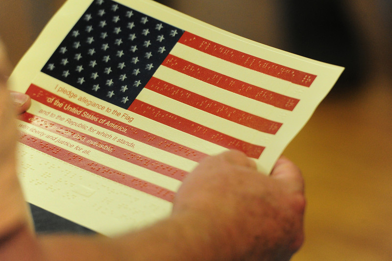 A veteran holds an American flag with the Pledge of Allegiance printed in English and Braille at the Estes Valley Senior Center on Wednesday. Disabled Resource Services handed out the flags for visually impaired veterans at the Assemblage of Honor, a chance for veterans to get together and talk about their experiences.