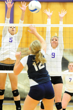 Erin Barker (5) and Amanda Dill (9) jump to block a hit against University on Thursday. The Ladycats hung tough against the Bulldogs, but dropped the match in three straight sets.