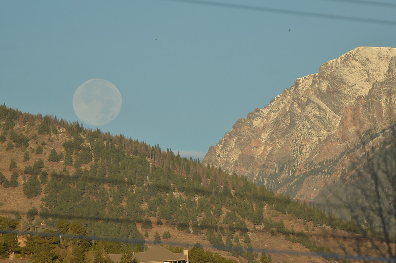 The Hunters' Moon dips down beyond Deer Mountain and Mt. Chapin on Tuesday. The moon got its name from Native Americans who would use the moon to hunt the game that was fattened up for the winter.
