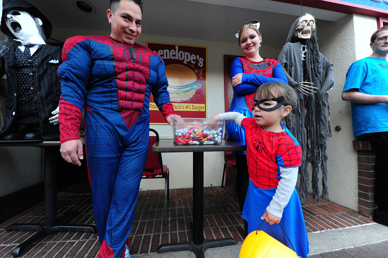 Raul, Jennifer,3, and Maria Rodriguez are a spider family in front of Penelope's on Wednesday. Families often take on a theme during the Elkhorn celebration.