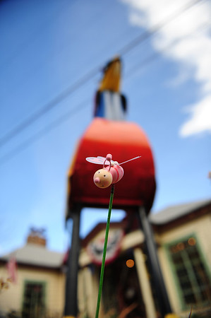 A decorative bee decorates the flower garden at the Glassworks on Tuesday. The bee is easy to miss with the giant metal rooster behind it.