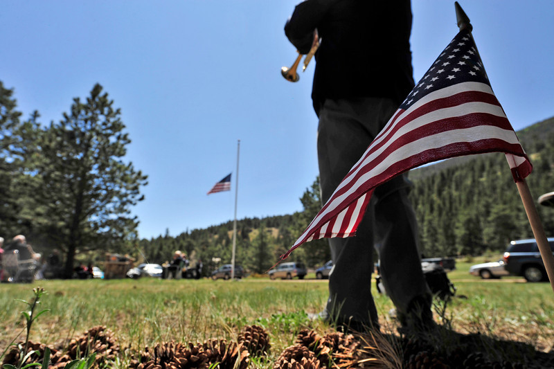 "Walt Hester | Trail Gazette<br /> Lauren Johnson plays ""Taps"" for the annual Memorial Day observance at the Estes Valley Memorial Gardens on Monday. The event drew a standing-room croud, in spite of the chilly wind blowing off the high peaks."