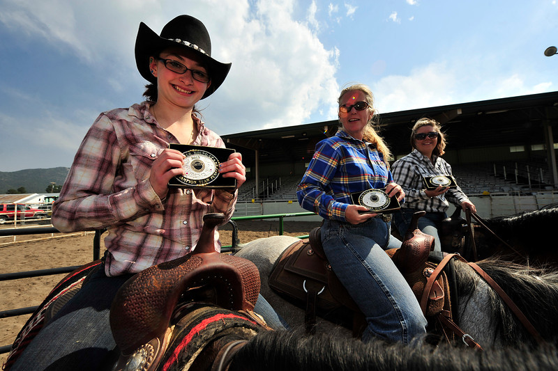 Walt Hester | Trail Gazette<br /> Tessa Shifty, 16, of Brighton, right, Leslie Gale of Littleton and Carrie Parman of Aurora, show off their Class 3, first place buckles at the team penning event at the Stanley Fairgrounds on Saturday. The event is a competition based on skills used in ranching everyday.