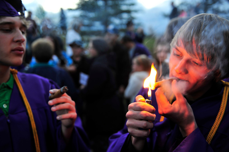 Walt Hester | Trail Gazette<br /> Joshua Hess lights his first post-comencement cigar after ceremonies at the YMCA of the Rockies on Friday. The Estes Park High School class of 2012 graduated 80 students, and filled the air with celebratory smoke.