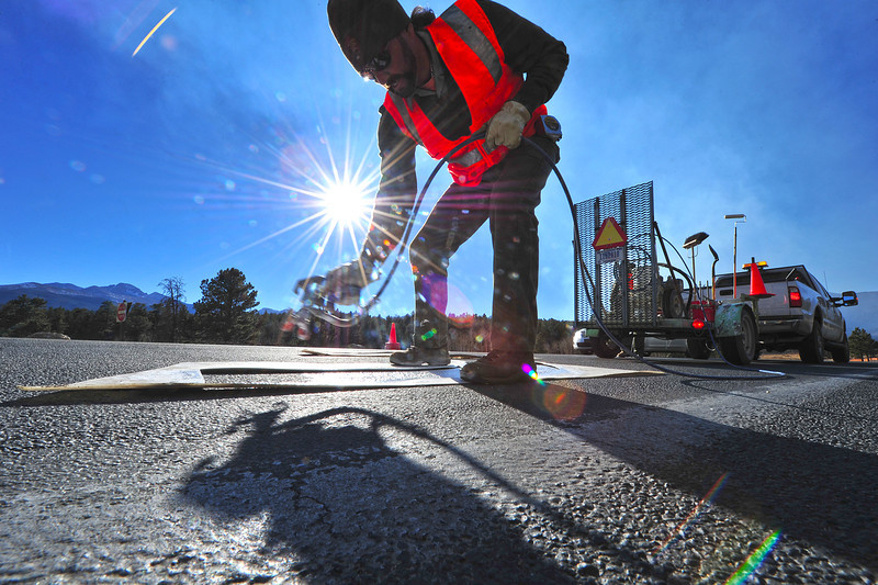 09EPNews Shiny New Park Paint.jpg Joel Jimenez sprays new paint on a turn lane at Bear Lake Road and Trail Ridge Road on Wednesday. Veterans will be able to see the new paint for free this weekend as the park is honoring veterans with free admission.