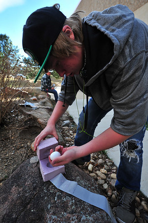 09EPStand Good Egg.jpg Matt Boyd of Estes Park checks his egg after it was dropped from the roof of the Estes Park High Schoolon Wednesday. Boyd carved out a place for his egg in two squares of foam insulation to keep it in tact.